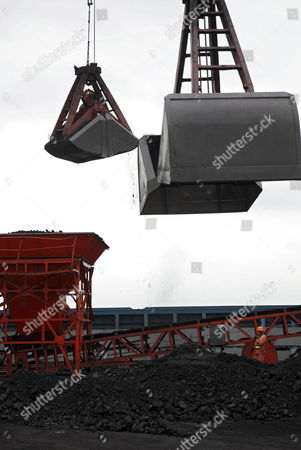 A Dock Worker Watches As Large Mechanical Scoops Carry Coal Onto Barges in Shanghai China on 08 September 2009 China the Biggest Producer of Coal Gets About 80 Per Cent of Its Electricity From Burning the Fuel Which Spews More Heat- Trapping Gases Than Natural Gas Or Oil China Has a 'Critical' Role in Developing Clean-energy Technologies Such As Carbon Capture Nobuo Tanaka Executive Director of the International Energy Agency Said in Beijing Earlier This Year China Shanghai