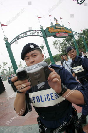 Police Film Falun Gong Protesters at Hong Kong Disneyland Park Monday 12 September 2005 Hong Kong Monday's Opening Ceremony Took Place Under High Security and Included Dignitaries From Hong Kong China and the Walt Disney Company Including Michael D Eisner Walt Disney Company Ceo; Robert a Iger Walt Disney Company President Chief Operating Officer and Ceo-elect; Zeng Qinghong Vice-president of the People's Republic of China; and Donald Tsang Chief Executive of the Government of the Hong Kong Special Administrative Region