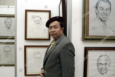 Stock Image of Chinese Artist Yuan Xikun Stands with His Personally Autographed Portraits of World Leaders Including Nelson Mandela (top L) Tony Blair (top R) and John Howard (bottom R) at His Gallery in Beijing Saturday 01 November 2003 Yuan Has Been Invited in Person to Draw Portraits of Over One Hundred Presidents and Plans to Draw Pakistani President Pervez Musharraf For the Second Time During His Five-day Visit to China Which Began Today