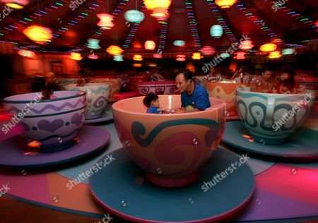 Father and Son Enjoy the Mad Hatter Tea Cups at Hong Kong Disneyland Monday 12 September 2005 Monday's Grand Opening Ceremony of Hong Kong Disneyland Included Dignitaries From Hong Kong China and the Walt Disney Company Including Michael D Eisner Walt Disney Company Ceo; Robert a Iger Walt Disney Company President Chief Operating Officer and Ceo-elect; Zeng Qinghong Vice-president of the People's Republic of China; and Donald Tsang Chief Executive of the Government of the Hong Kong Special Administrative Region