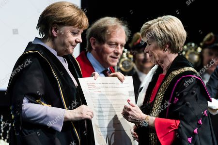 German Chancellor Angela Merkel, left, is given an honorary doctorate by the Rector of the University of Leuven Rik Torfs, second left, and the Rector of the University of Ghent Anne De Paepe, during an academic ceremony in Brussels on . Merkel received the honorary doctorate for her diplomatic and political efforts to develop the political strength of Europe, and to defend the values that allow Europe to find unity in diversity