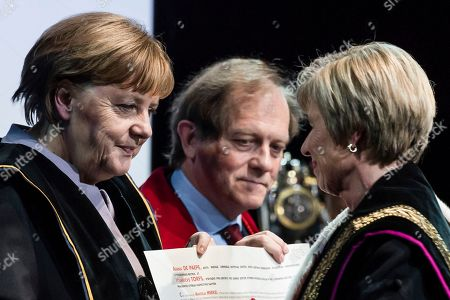 German Chancellor Angela Merkel, left, is given an honorary doctorate by the Rector of the University of Leuven Rik Torfs, center, and the Rector of the University of Ghent Anne De Paepe during an academic ceremony in Brussels on . Merkel received the honorary doctorate for her diplomatic and political efforts to develop the political strength of Europe, and to defend the values that allow Europe to find unity in diversity
