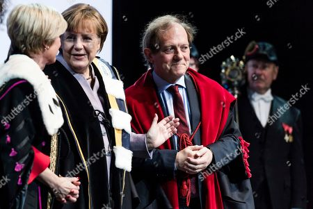 German Chancellor Angela Merkel, second left, is given an honorary doctorate by the Rector of the University of Leuven Rik Torfs, right, and the Rector of the University of Ghent Anne De Paepe during an academic ceremony in Brussels on . Merkel received the honorary doctorate for her diplomatic and political efforts to develop the political strength of Europe, and to defend the values that allow Europe to find unity in diversity