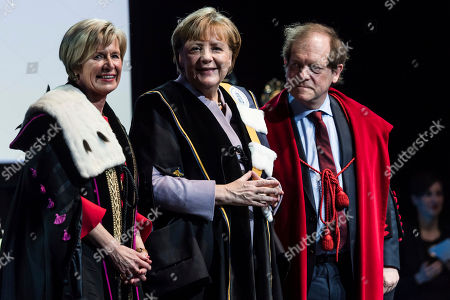 German Chancellor Angela Merkel, center, is given an honorary doctorate by the Rector of the University of Leuven Rik Torfs, right, and the Rector of the University of Ghent Anne De Paepe during an academic ceremony in Brussels on . Merkel received the honorary doctorate for her diplomatic and political efforts to develop the political strength of Europe, and to defend the values that allow Europe to find unity in diversity