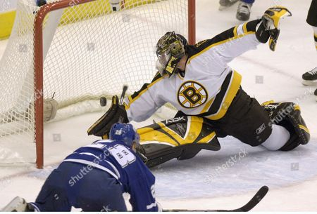 Toronto Maple Leaf Forward Tie Domi (l) Scores His Team's First Goal Against Boston Bruin Goalie Andrew Raycroft During a First Period Action at the Air Canada Centre in Toronto Canada On Monday 24 October 2005