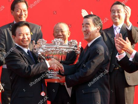 Stock Picture of Horse Owner Leung Kai Fai Recieves a Trophy From Tu Ming De Vice President of the China Olympic Committee For Winning the Hong Kong Mile at the Shatin Hong Kong International Races 14 December 2003
