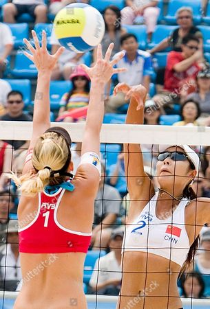 China's Zhang Wen Wen (r) Spikes the Ball Against Switzerland's Sarah Schmoker (l) Block During Their Semi-final Match at the Fivb Beach Volleyball Women's Challenge at Chaoyang Park Beach Volleyball Ground Stadium in Beijing China 18 August 2007 the Tournament is Part of a Series of Olympics Test Events Being Held in Beijing As the City Prepares For the Games in 2008