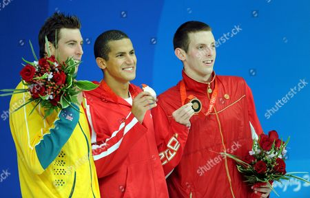 Gold Medal Winner Oussama Mellouli (c) From Tunisia is Flanked by Silver Medalist Grant Hackett (l) of Australia and Bronze Winner Ryan Cochrane of Canada During the Medal Ceremony in the Men's 1500m Freestyle Final at the at the National Aquatic Center at the Beijing 2008 Olympic Games Beijing China 17 August 2008