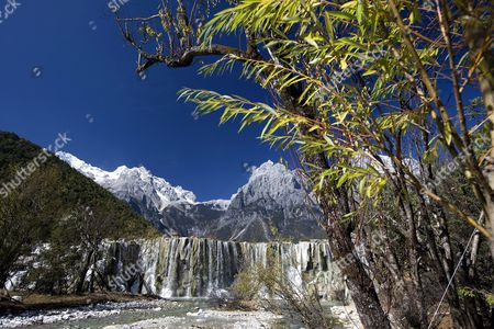 A Man Made Waterfall Beneath the Peak of Yulong (jade Dragon) Snow Mountain Town of Lijiang in Yunnan Province Southwest China 31 October 2007 the 5596 Meter Peak of the Perpetually Snow Covered Mountain Has Never Been Conquered Despite Attempts by Teams From China Usa Japan and Elsewhere and with a High Casualty Rate the Local Government Has Banned Future Attempts the Mountain is Also Remarkable For Having a Glacier the Closest to the Equator of Any But Moving As Much As 500 Meters Annually