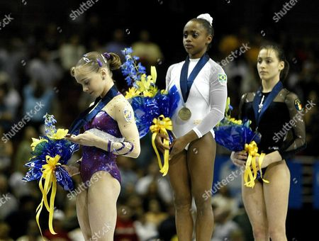 Spain's Elena Gomez (l) Checks out Her Bronze Medal As She Waits On the Victory Stand with Gold Medalist Daiane Do Santos (c) of Brazil and Romanian Silver Medalist Catalina Ponor (r) After Their Competition in the Floor Exercise at the World Gymnastic Championships in Anaheim California Sunday 24 August 2003 Epa Photo/epa/jack Smith United States Anaheim