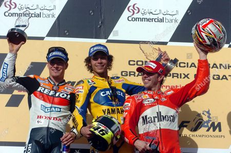 Winner of the Qatar Motorcycle Grandprix Italian Camel Yamaha Rider Valentino Rosi (c) Flanked by American Repsol Honda Rider Nicky Hayden (l) and Third Place Winner Italian Ducati Rider Loris Capirosi Celebrate Their Victory After the Award Ceremony of the Grand Prix of Qatar Race Held at the Lusail International Circuit in Doha Qatar Saturday 08 April 2006