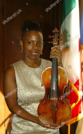 New York Jazz Violinist Regina Carter Poses Next to an Italian Flag with the Priceless Paganini Guarneri Del Gesu Violin at a Press Conference Monday 03 November 2003 at the Italian Cultural Institute in New York the Violin Which is Genoa National Treasure Was Owed by Italy's Famous Violinist Niccolo Paganini