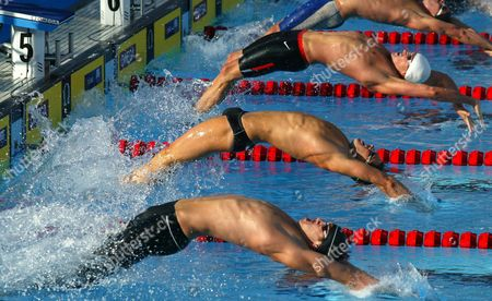 Swimmers From Left to Right Matt Grevers Lenny Krayzelburg Dan Westcott and Jeff Rouse Jump Back As They Start the Semifinal of the 100 Meter Backstroke During the U S Olympic Team Trials at the the Long Beach California Swim Center in Long Beach California Thursday 08 July 2004