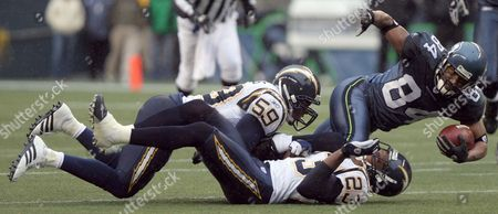 Seattle Seahawk Receiver Bobby Ingram (r) is Caught by San Diego Charger Defenders Donnie Edwards (l) and Quentin Jammer (c) After a Pass Completion During First Quarter Play of Their Game in Seattle Washington Sunday 24 December of 2006