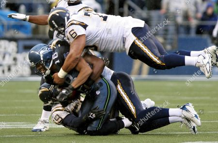 San Diego Chargers 348 Pound (about 148 Kg) Defensive Tackle Jamal Williams (top) Helps Teammate Donnie Edwards (bottom) Stop Seattle Seahawk D J Hackett On a Pass Play During Second Quarter Play of Their Nfl Game in Seattle Washington Sunday 24 December of 2006