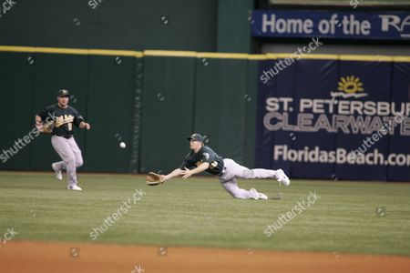 Oakland A's Right Fielder David Putnam (r) Makes a Diving Catch in Front of Teammate Chris Snelling (l) For the Third out During the First Inning of Their Game Against the Tampa Bay Devil Rays at Tropicana Field in St Petersburg Fl 06 May 2007 the A's Won the Game 5-3