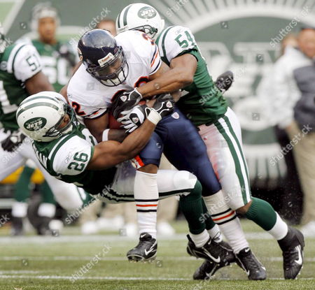 Stock Photo of The Bears' Cedric Benson (c) is Brought Down by the Jets' Erik Coleman (l) and Victor Hobson (r) During the First Half of the Game Between the Chicago Bears' and the New York Jets at the Meadowlands in East Rutherford New Jersey On Sunday 19 November 2006