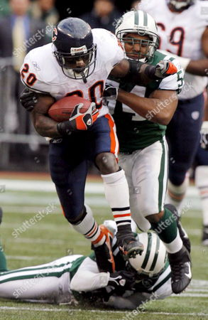 Chicago Bears' Running Back Thomas Jones (l) Looks For Yardage Past New York Jets Linebacker Victor Hobson (r) During the First Half of the Chicago Bears' 10-0 Victory Over the Jets at the Meadowlands in East Rutherford New Jersey On Sunday 19 November 2006