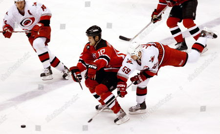 The Devils' Erik Rasmussen (c) Battles For the Puck with the Hurricane's Chad Larose (r) and Kevyn Adams (l) During the First Period of Game Four of the Round Two Playoffs Between the Carolina Hurricanes and the New Jersey Devils at Continental Airlines Arena Wednesday 10 May 2006 in East Rutherford New Jersey