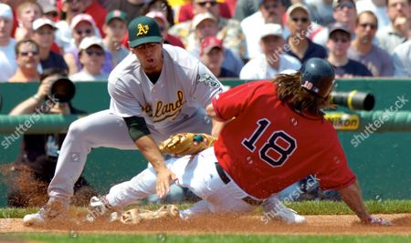 Boston Red Sox Johnny Damon (r) Safely Slides Into Third Infront of Oakland Athletics Third Baseman Eric Chavez (l) in the Second Inning at Fenway Park in Boston Massachusetts Wednesday 11 May 2005