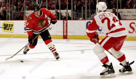 Chicago Blackhawks Brent Seabrook (l) Tries to Score Against Detroit Red Wings Chris Chelios (r) During the First Period of Their Nhl Ice Hockey Game at the United Center in Chicago Illinois Usa 12 April 2009