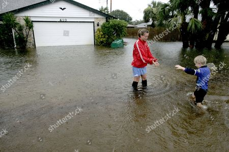 Julie Stern (l) Helps Her Brother Josh (r) Walk Through Flood Waters to Get to Their Grandmother's House in Indialantic Florida Usa 20 August 2008 Over 15 Inches of Rain Fell in Some Parts of Florida Causing Streets and Homes to Be Flooded