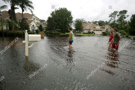 Stock Image of Derek Phillips (l) Katie Bobe (c) and Zach Fairchild (r) Walk Down a Flooded Soft Shadow Lane in Debary Florida Usa 22 August 2008 Record Rain From Tropical Storm Fay Fell in Some Parts of Florida Causing Many Residents to Evacuate Their Homes