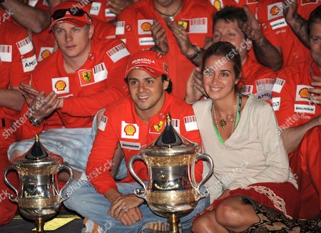 Brazilian Formula One Driver Felipe Massa (c) of Ferrari His Wife Rafaela Bassi (r) and His Team-mate Finnish Kimi Raikkonen (l) Pose Behind of the Trophies After Massa Won the Bahrain Grand Prix at the Sakhir Circuit Near Manama Bahrain On 06 April 2008