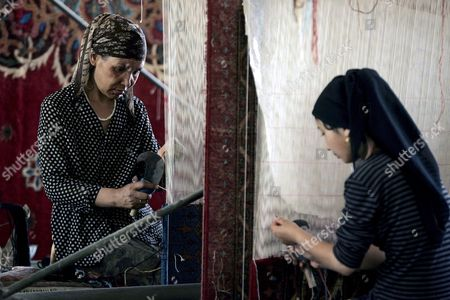 Women of the Islamic Uighur Ethnic Group Work in the Blanket Weaving Workshop of a Factory Making Hand-made Carpets in Khotan China's Xinjiang Uighur Autonomous Region 21 June 2008 Khotan is Located On the Remote Southern Edge of the Taklamakan Desert and For Centuries Was an Important Trading Post On the Old Southern Silk Road the City Has a History of Making Some of the Most Exquisite Carpets and Silk Since the 5th Century Ad Khotanese Carpets Are Still an Important Export Product Today in an Otherwise Economically Depressed Area