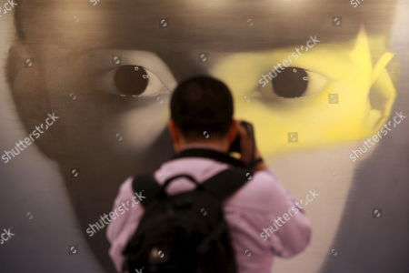 A Photographer Takes a Photo in Front of a Painting 'Untitled' by Chinese Printer Zhang Xiaogang is Displayed During a Sotheby's Press Preview in Hong Kong China 02 April 2009 the Painting Will Be Sold at an Auction in Hong Kong On 06 April and Estimated at 4 to 5 5 Million Hong Kong Dollars