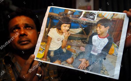 Rafiq Qureshi Father of Child Actor of 'Slumdog Millionaire' Rubina Ali Qureshi Shows the Photo of His Daughter and Other Child Actor Mohammed Azharuddin Ismail in Mumbai India 23 February 2009 the Mumbai-based Movie About the Unlikely Rise of an Inconsequential Indian Pauper to Win India's Most Popular Game Show Won an Even More Remarkable Victory When It Swept Eight Oscars Including the Most Coveted One of All For Best Picture of the Year the Movie Has Already Earned Close to $160 Million at the Global Box Office and the Oscar Win Will Surely Boost Its Earning Significantly