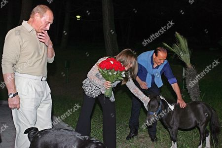 Italian Premier Silvio Berlusconi (r) and His Wife Veronica Lario (c) Stroke a Pony Prior to the Meeting with Russian President Vladimir Putin (l) in Putin's Residence Bocharov Ruchei in at the Black Sea Resort of Sochi Sunday 28 August 2005