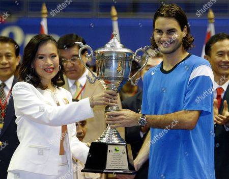 Stock Image of Roger Federer From Switzerland (r) Holds the King's Cup Thailand Open Trophy with Thai Princess Ubol Ratana the Oldest Child of King Bhumibol Adulyadej and Queen Sirikit of Thailand After Federer Beat Opponent and World Number Two Andy Roddick Usa 6-4 6-0 in the Final of the Thailand Open in Impact Arena Stadium Bangkok Thailand Sunday 03 October 2004