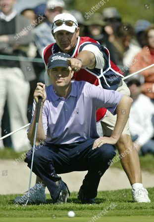 As Us Davis Love Iii Studies His Putt As His Caddie John Burke (background) Points Something out On the 18th Green During His Morning Match with Fellow American Phil Mickelson Saturday 28 February 2004 at the Accenture World Match Play Championship in Carlsbad Calif Love Defeated Michelson 1-up to Advance