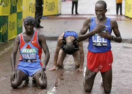 The Winner of the Flora London Marathon Martin Lel From Kenya (r) Kneels On the Ground Next to Kenyan Sammy Wanjiru (l Second) and Third Placed Moroccan Abderahin Gouniri From Morocco (background) 13 April 2008 Martin Lel Finished the Race in 2 Hours 5 Minutes and 15 Seconds Around 36 000 Runners Competed with Elite Athletes Celebrities and Fundraisers Through the Streets of Central London and Along Famous English Landmarks