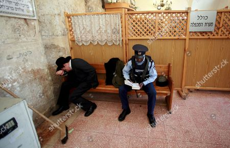 An Ultra-orthodox Jew and an Israeli Policeman Praying at the Entrance to the Cave of the Patriarchs an Ancient Site Holy to to Both Jews and Moslems in the West Bank City of Hebron On 23 November 2008 to Jews the Cave Complex Contains the Burial Sites of Abraham Sarah Isaac Rebecca Jacob and Leah As Well As Adam and Eve to the Moslems It is the Burial Site of Ibrahim and Was Converted Into a Mosque in About the Year 1 200
