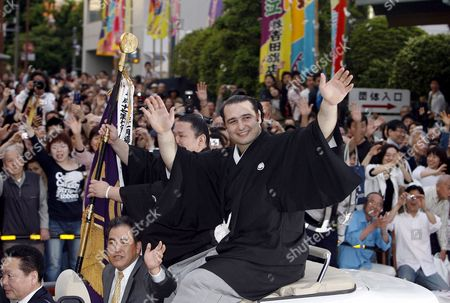 Accompanied by Sumo Wrestler Kotokasuga Bulgarian Ozeki Kotooshu (r) Waves to Fans From an Open Car During a Parade Outside the Kokugikan Sumo Arena in Tokyo Japan 25 May 2008 ?kotooshu Entered the Sumo History As He Became the First European Wrestler to Win the Emperor's Cup at a Grand Sumo Tournament