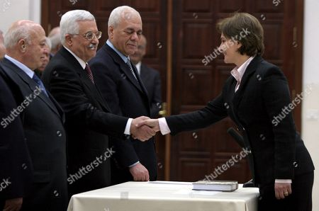 One of Two Palestinian Women in the New 'Reformist' Government Minister Without Portfolio Hind Khoury (r) Shakes Hands with Palestinian President Mahmoud Abbas (abu Mazen) As Prime Minister Ahmed Qureia (l) Looks On Along with Palestinian Official Tayeb Abd Al Rahim During the Ceremony Swearing-in the New Government On Thursday 24 February 2005 in the 'Muqatas' in the West Bank Town of Ramallah the New Government is Comprised of 24 Ministers 17 of Whom Are New to the Government