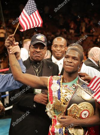 Welterweight Champ Cory Spinks (r) Wears the Title Belt and Holds an American Flaz As His Father Leon Spinks a Former Heavyweight Champion (l) Enjoys the Moment After Spinks Defeated Challenger Miguel Angel Gonzalez of Meixco to Retain the Title in Las Vegas Saturday 04 2004 Spinks Won by Unanimous Decision