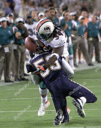 Miami Dolphin Running Back Ricky Williams (34) Fumbles the Ball After He Was Hit by San Diego Charger Donnie Edwards (59) in the Second Quarter the Nfl Monday Night Game Was Moved to Tempe Arizona After Wild Fires Rage Thoughout San Diego