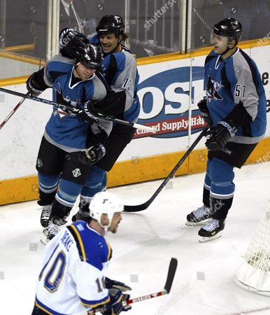 Stock Photo of San Jose Sharks Mark Smith (l) is Greeted by Team Mates Todd Harvey (c) and Marcel Cog (r) After Scoring a Goal Against the St Louis Blues As Blues' Dallas Drake Looks On During Game Five of the Second Period of the Western Conference Nhl Playoffs at Hp Pavilion in San Jose California Thursday 15 April 2004 the Sharks Defeated the Blues 3-1 to Advance to the Next Series