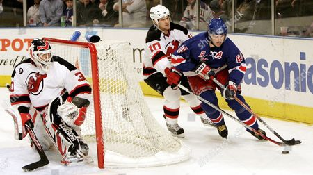 The Devils' Erik Rasmussen (c) Tries to Steal the Puck From the Rangers' Jaromir Jagr (r) As Martin Brodeur (l) Watches During the First Period of Game Three of the Round One Playoff Match Up Between the New York Rangers and the New Jersey Devils at Madison Square Garden Wednesday 26 April 2006 in New York