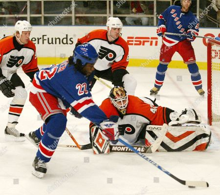 Stock Photo of New York Rangers Anson Carter Tries to Control the Puck in Front of Philadelphia Flyers Goaltender Robert Esche On Thursday 22 January 2004 During Second Period Action at Madison Square Garden in New York Flyers Defeated the Rangers 4-2