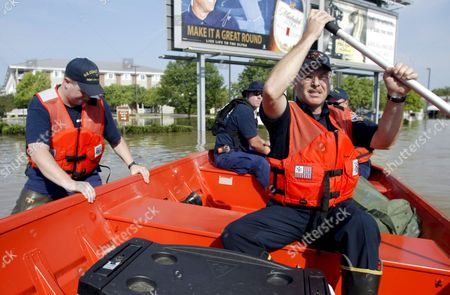 Members of the United States Coast Guard Ian Ryan Left and Joel Brown Center and Findlay Fireman Mark Sanders Set out to Patrol the Flooded Waters of the Blanchard River After Heavy Rains Caused Flooding in Findlay Ohio Usa 23 August 2007 the Blanchard River Was Close to 7 Feet Above Flood Stage at Findlay Yesterday Morning the Highest Since a 1913 Flood