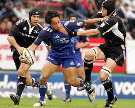 Auckland Blue's Ben Atiga Gets Tackled by Stormers No8 Joe Van Niekerk(r) and Centre De Wet Barry During the Super 12 Rugby Game Between the Blues and Stormers in Cape Town South Africa Saturday 23 April 2005 the Blues Won 37-24