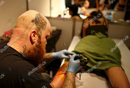 A Woman is Worked On by Tattoo Artist David Steele From the Usa (l) at the Southern Ink Exposure Tattoo Convention in Cape Town South Africa 24 January 2009 the 2009 Southern Ink Exposure Tattoo Convention From the 23 to 25 January is the Biggest Tattoo Convention in the Southern Hemisphere Organisers Have Been Overwhelmed by the Huge Response to More Than 50 Top Local and International Artists Working in One Space Over the Three Day Event