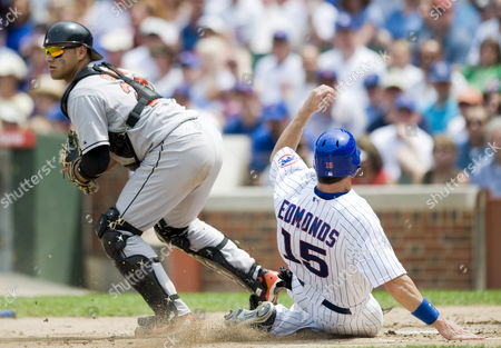 Baltimore Orioles Catcher Guillermo Quiroz (l) Steps Away From Home Plate After Forcing out Chicago Cubs Outfielder Jim Edmonds (r) As Edmonds Tries to Score On a Bases-loaded Grounder Hit by Cubs Pitcher Jason Marquis in the Second Inning at Wrigley Field in Chicago Illinois Usa 26 June 2008 the Orioles Defeated the Cubs 11-4