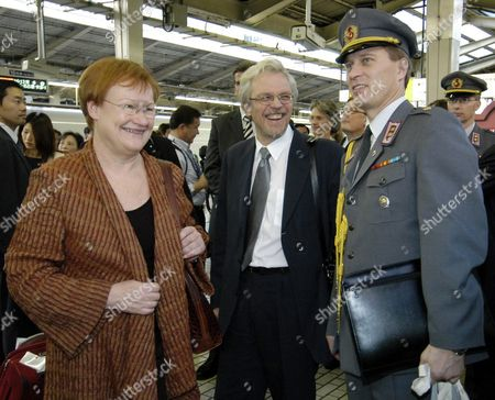 Finnish President Tarja Halonen (l) and Her Husband Dr Pentti Arajarvi (c) Smile Before Boarding the Shinkansen Train at Tokyo Station Friday 22 October 2004 President Halonen Departed For an Overnight Stay in Kyoto During Her State Visit to Japan 19-24 October