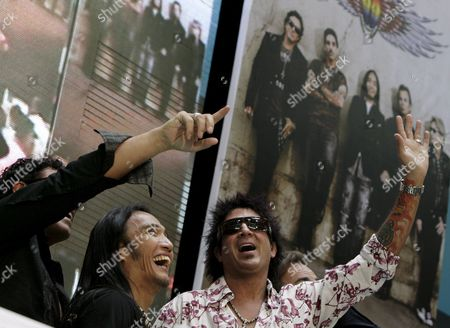 Filipino Singer Arnel Pineda (2-l) and Deen Castronovo (r) of the Rock Band 'Journey' Wave During a Press Conference in Quezon City East of Manila Philippines 02 March 2009 Filipino Singer Arnel Pineda is the Band's New Lead Vocalist Journey is in Manila For a One Night Concert