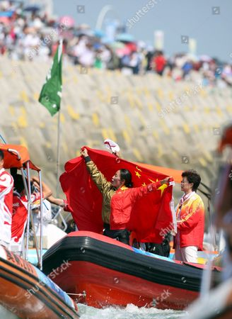 Stock Photo of Yin Jian of China Celebrates Her Gold Medal Holding the Chinese Flag Giving China Its First Ever Olympic Sailing Gold in the Womens Rs:x Women's Windsurfing Event in Qingdao China 20 August 2008 Italys Alessandra Sensini Won the Silver Medal and Bryony Shaw of Great Britain Won Bronze